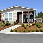 Well manicured landscaping at home in Heritage Village. Home with covered front porch and 2 large hanging pots of flowers. Small green shrubs are planted on outskirts of lawn along driveway and street. Corner lot.