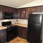 Updated kitchen with mahogany cabinets, beige marble counter tops, and beige tile back-splash. Includes all black appliances.
