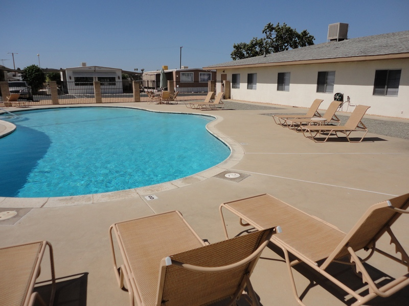Outdoor pool within the mobile-home community. Surrounded by multiple lounge chairs for relaxation out in the sun.