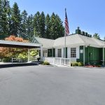 Heritage Village, an all age manufactured home community in Beaverton. Sales office inside green building and marked with red Sales Office sign pointing to the right. Large American flag on tall flagpole. Very tall trees in background. Clean, paved driveway up to building.