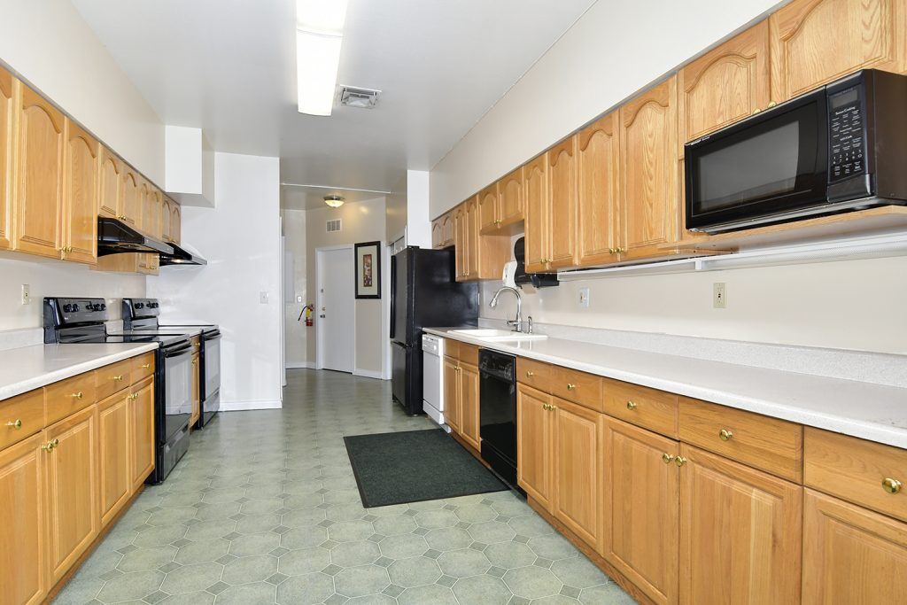 Large community kitchen with black appliances. Lots of cabinets and white countertops.