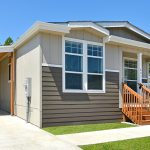New manufactured home for sale. Covered carport with shed at end. Covered front porch. Painted gray and tan with trimmed green grass.