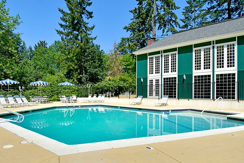 Heritage Village, an all age manufactured home community, has swimming pool with lounge chairs, tables and umbrellas. Tall lush trees all around. Green clubhouse with white shutters next to pool.