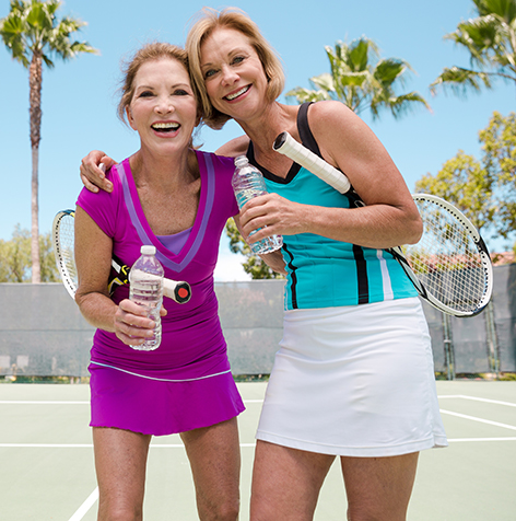 Two women drinking water after a tennis game on outdoor tennis court on beautiful sunny day. Palm trees swaying.