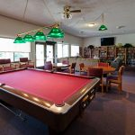 Game room with a pool table and couple tables with chairs to play cards.