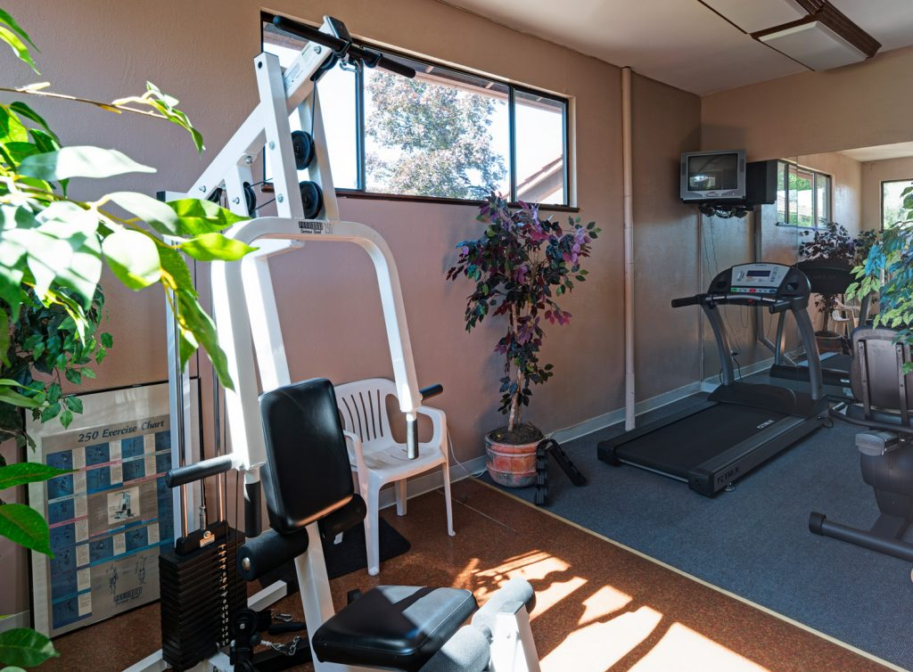Fitness center with weight machine, treadmill and stationary bike. Small TV mounted to wall.