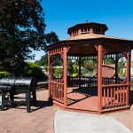 Wood gazebo with black BBQ next to it.