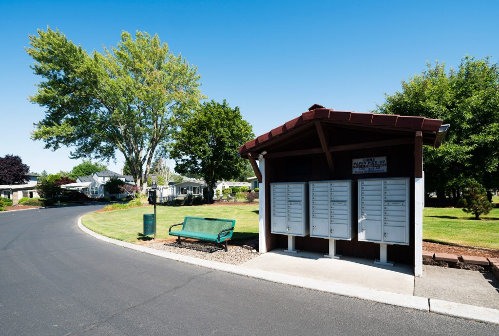 Clean paved streets and lots of green trees, trimmed grass surround the mailboxes. Small bench to sit on next to mailboxes.
