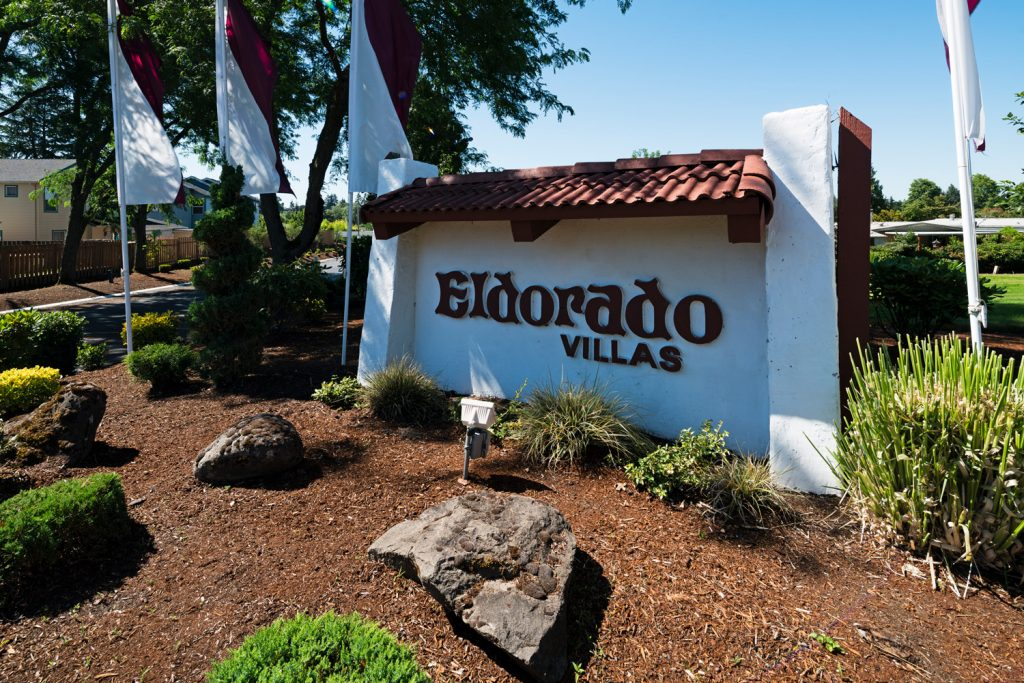 Eldorado Villas in Tigard, OR is a 55 plus manufactured home community with a sign at the entrance and purple and white flags.