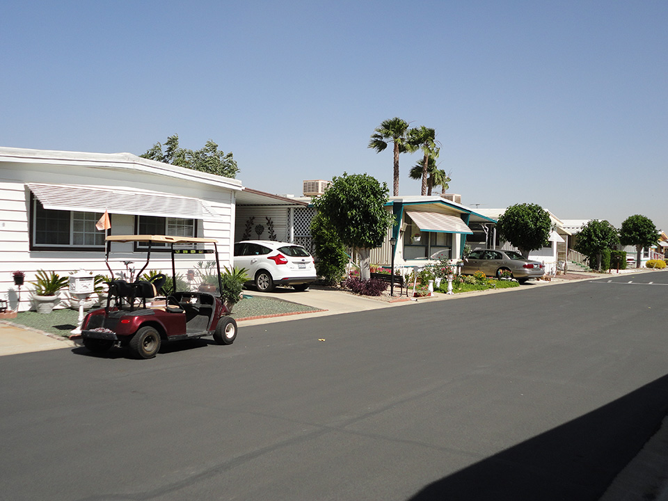 Street view of mobile-home community. Offers welcoming atmosphere with open streets accessible for all cars including resident owned golf carts.
