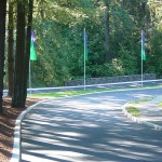 Windy roads in and out of Heritage Village. Tall trees along the roads. Tall green and blue flags are in the median. Lots of shade.