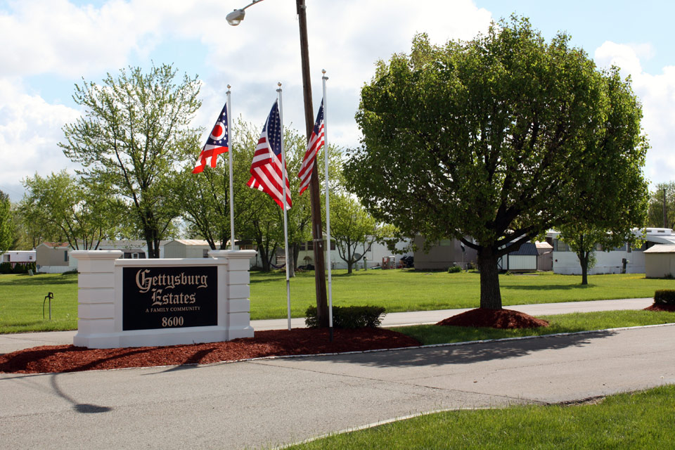 Gettysburg Estates is an all age community with large stone marquee at entrance. American flag flies high on flag pole. Beautiful lush full trees and green grass at entrance. Manufactured homes in the background.