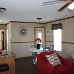 New home with wood flooring and open concept. Eat in area off the kitchen with round, white table and 3 gray chairs. Red and gray cushioned chairs with multi-colored decorative pillows in living area.