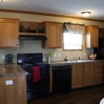 Brand new kitchen with wood flooring and black appliances. Wood cabinets and granite countertops. Small breakfast nook with a couple bar stools.