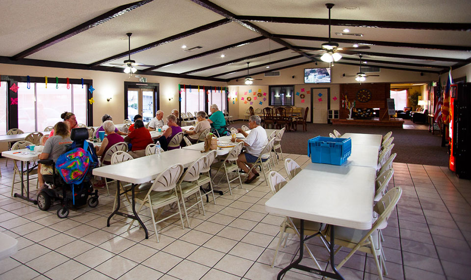 A group of older residents sit at long tables with chairs inside the clubhouse and eat lunch while creating some arts and crafts. A big screen TV mounted to the wall is on while they work.