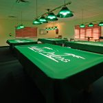 Billiards room offering 4 pool tables, chairs, tables, 2 dart boards, and lighting above each table