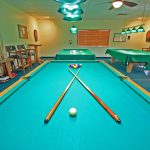 The billiards room has 4 pool tables and chairs and tables. The rules of play are hung on the wall above pool game supplies. Also 2 dartboards and lighting with ceiling fan.