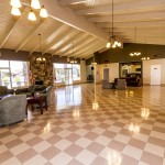 Large community hall with high vaulted ceilings, hanging lights, and checkered floors. Multiple windows provide natural light creating an open space.