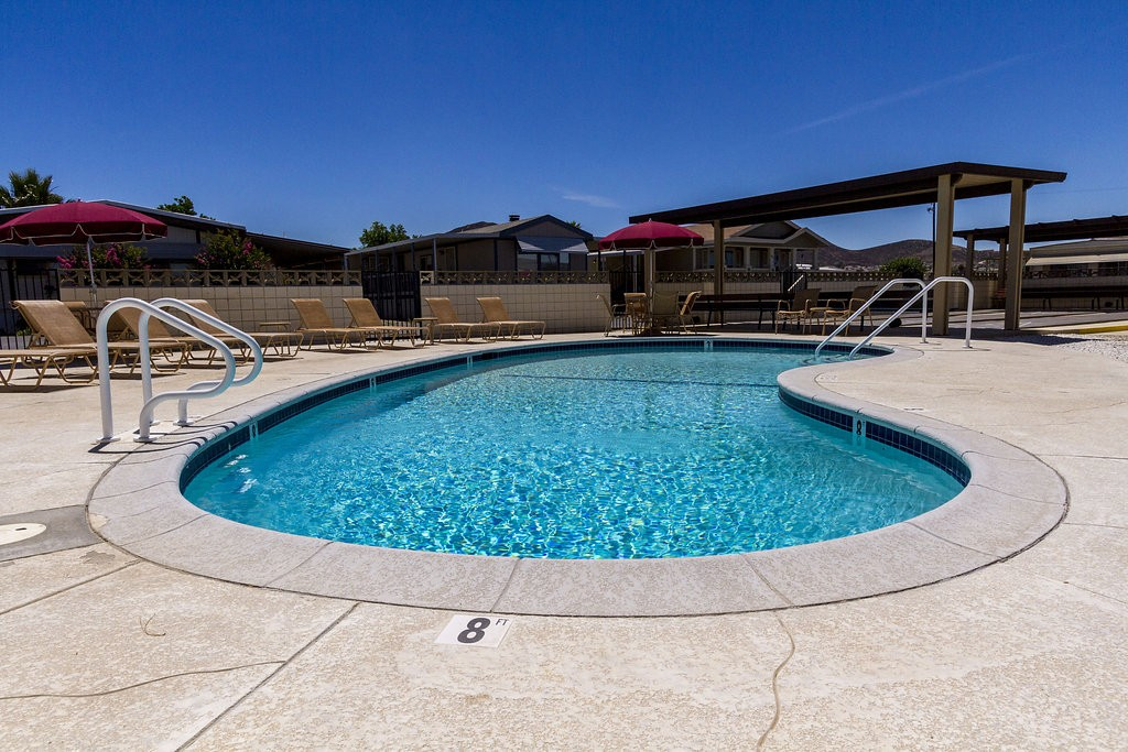 Outdoor pool surrounded by lounge chairs. Provides a space to enjoy a day under the sun with your friends and family.