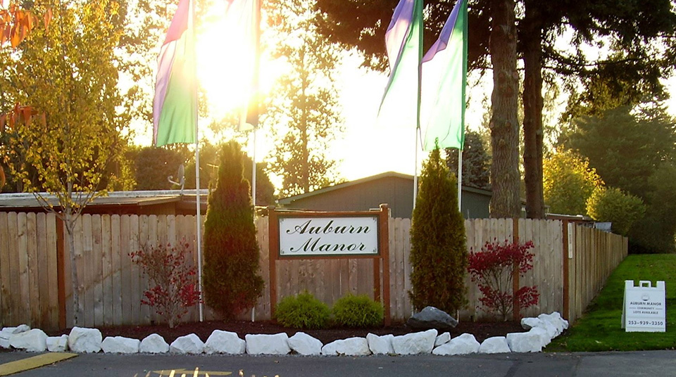 Front entrance sign to Auburn Manor that sits in front of a wooden fence with beautiful, tall trees behind. Four flags and two bushes sound the sign to draw attention.