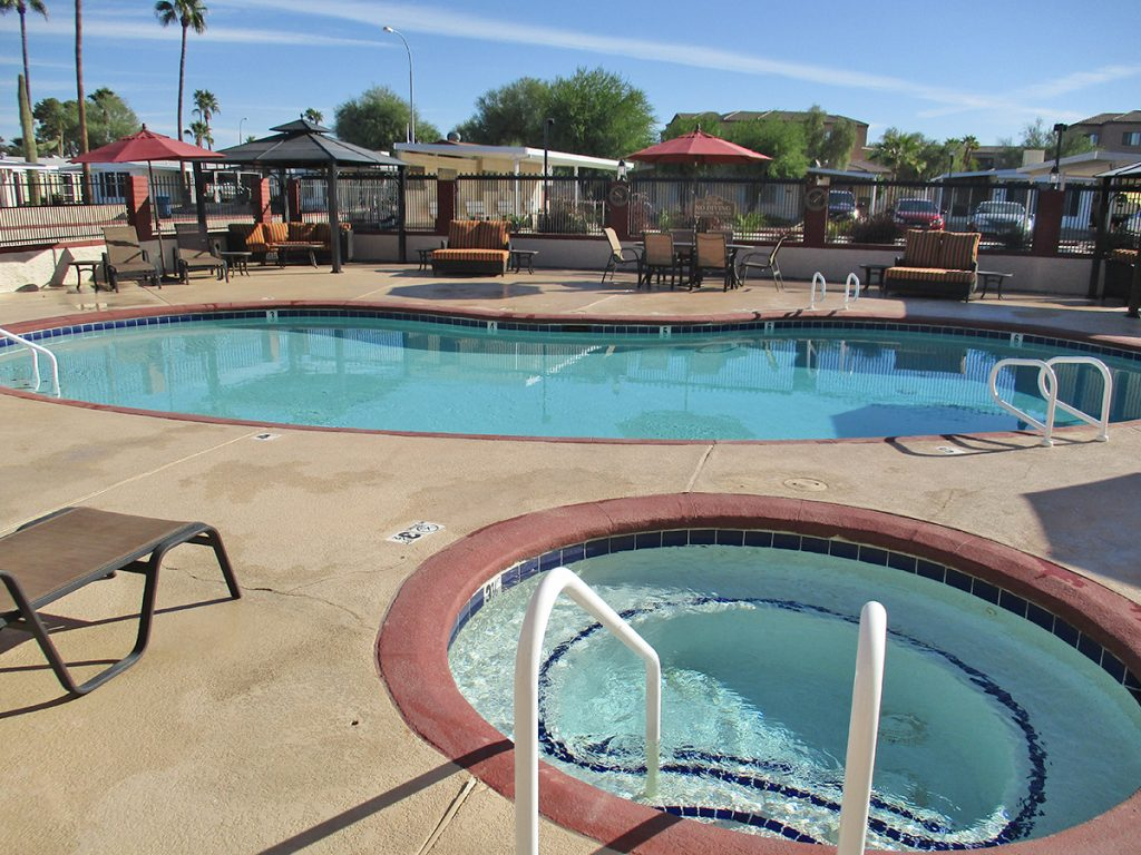 Outdoor swimming pool and Jacuzzi with lounge chairs and cabanas at Holiday Palms a 55 plus ...