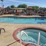 Outdoor swimming pool and Jacuzzi with lounge chairs and cabanas at Holiday Palms a 55 plus manufactured home community in Mesa Arizona.