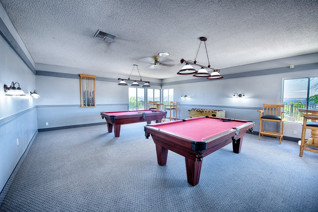 Game room with two pool tables and foosball.
