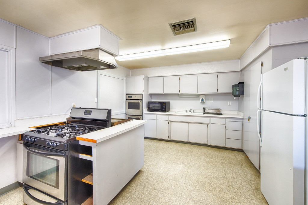 Full size kitchen inside clubhouse with 3 ovens, microwave, fridge and lots of cabinet space.