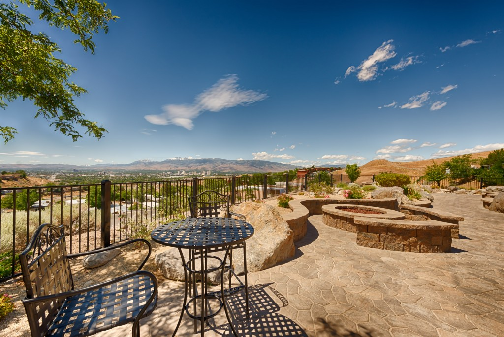 A bistro table and chairs outside offer a wonderful view of the mountains and downtown Reno. Stone firepit with seating around it.