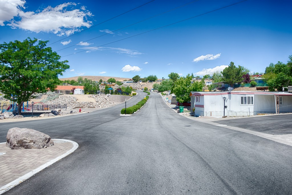Wide, clean, paved roads throughout the manufactured home community that sits on a hillside.