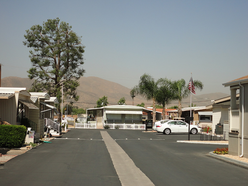 Bel Air Estates, an active 55 plus community in Menifee, California has wide, clean paved streets. Rolling hills in background.