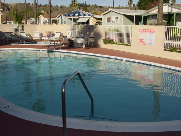 One of two outdoor pools in the community enclosed by a gate. A spa lies adjacent to the pool, with lounge chairs surrounding the perimeter of the outdoor area.