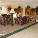 One of two community centers with green and red patterned, love-seat sofas. An open space for residents to relax or read a novel from the stocked bookshelves.