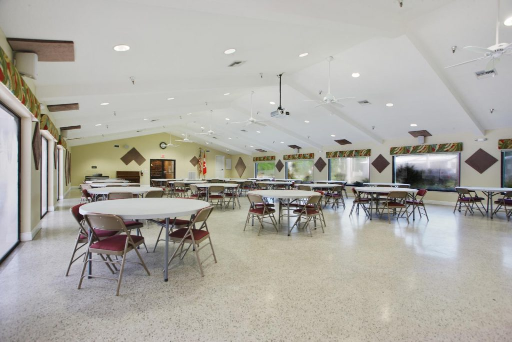Large clubhouse with vaulted ceilings and ceiling fans. Round table with chairs cover the floor. Lots of windows on both sides.