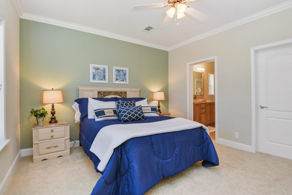 Lamplighter Village, an upscale, resort style 55+ manufactured home community, has new homes for sale. A bedroom with adjoining bathroom. Light tan carpet fills the bedroom and crown molding runs the top of walls where one is painted sage green and the others a light grey. Two end tables with two lamps are on each side of the bed which has a blue comforter and white throw blanket at the end. Ceiling fan equipped in the room.