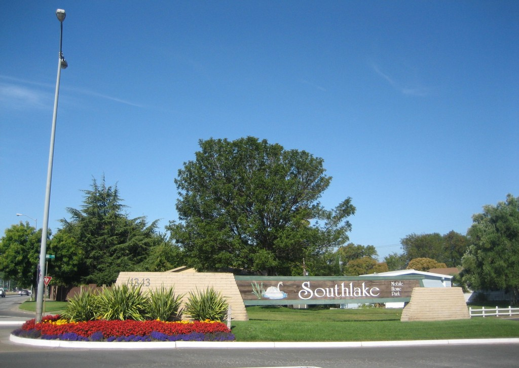Large front entrance sign into Southlake Mobile. Surrounded by beautiful red, purple, and yellow flowers and well maintained grass.