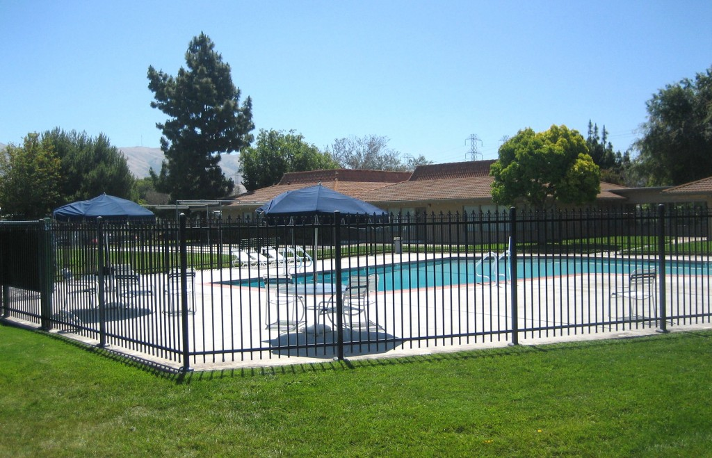 Outdoor, full-sized community pool enclosed by a black fence. Surrounded by lounge chairs and shaded tables with additional seating. Open for residents to enjoy with family and friends under the sun.
