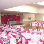 Open and large community hall within the community center. Space for residents to host events and parties as pictured. Decorated for a residents events with multiple round tables surrounded by chairs decorated with a pink and white theme throughout.