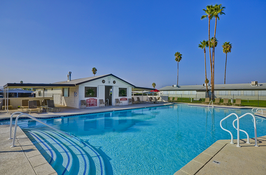 Beautiful, large outdoor pool opened year-round for residents to enjoy. Enclosed within a gate and surrounded by lounge chairs and palm trees.