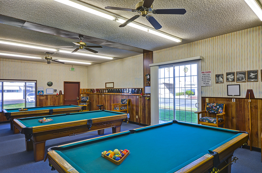 Billiards room equipped with three pool tables for residents to freely use. Old wood panels line the lower half of the walls to give an old saloon feel.