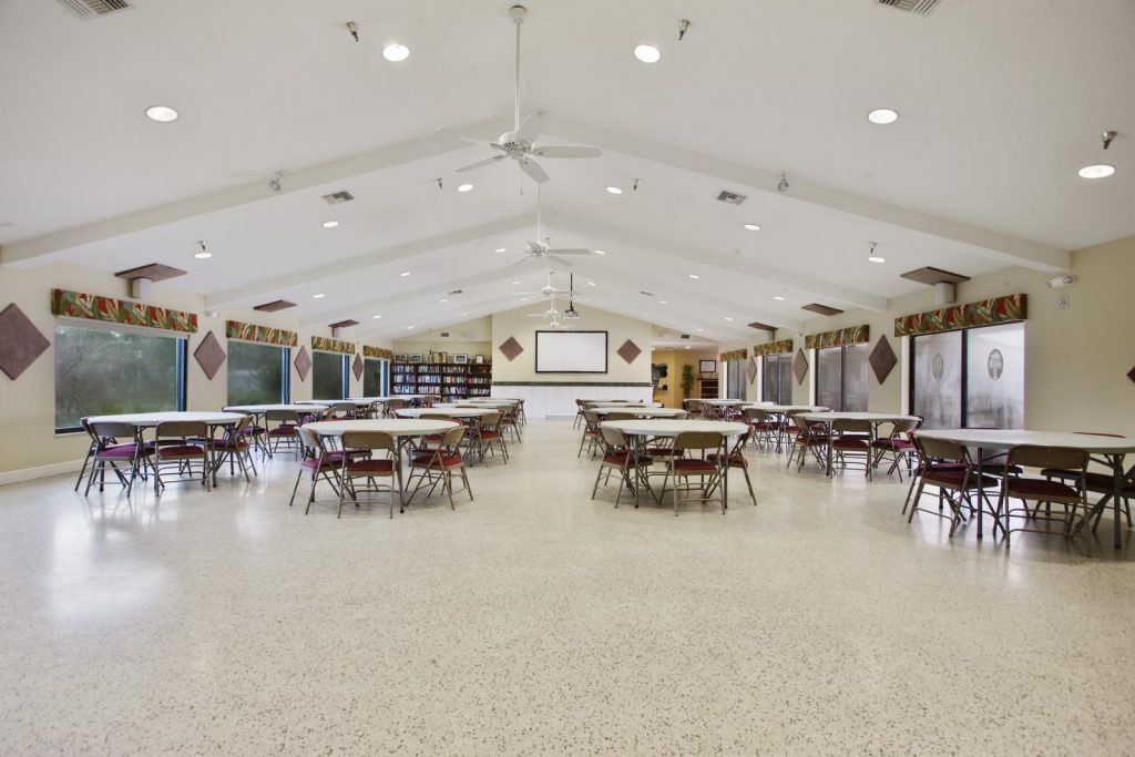 At one end of the clubhouse has large screen mounted to wall. A projector hangs from ceiling. Round tables with chairs are set up along the floor.