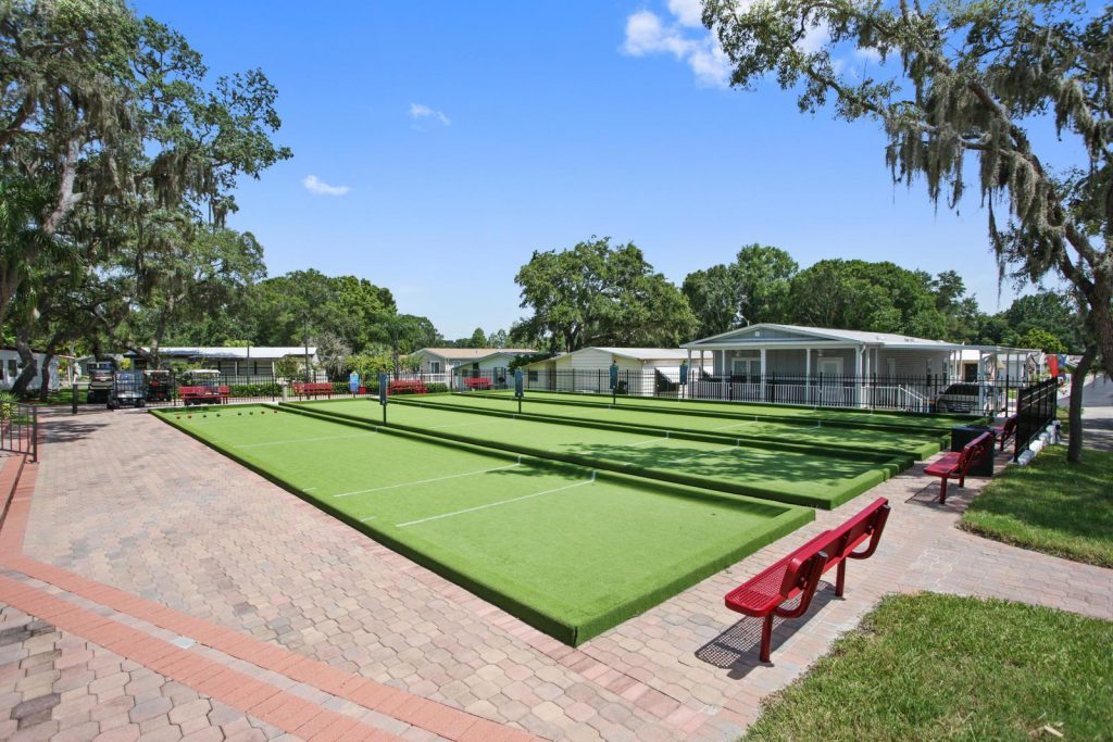 Clean bocce ball fields with red benches for seating are an amenity at Island in the Sun.