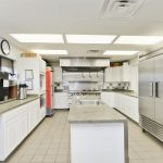 Beautiful modern commercial kitchen in clubhouse with all stainless steel appliances and plenty of white cabinets for storage. Long island with sink in the middle.