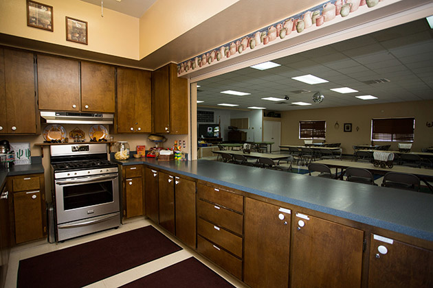 A kitchen inside the clubhouse with a stainless steel stovetop and oven and plenty of brown cabinets and counter space.