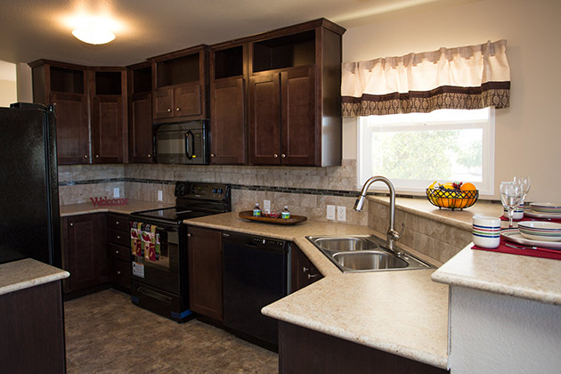 Brand new beautiful kitchen with black appliances like fridge, microwave, oven, and dishwasher. Dark wood kitchen cabinets.