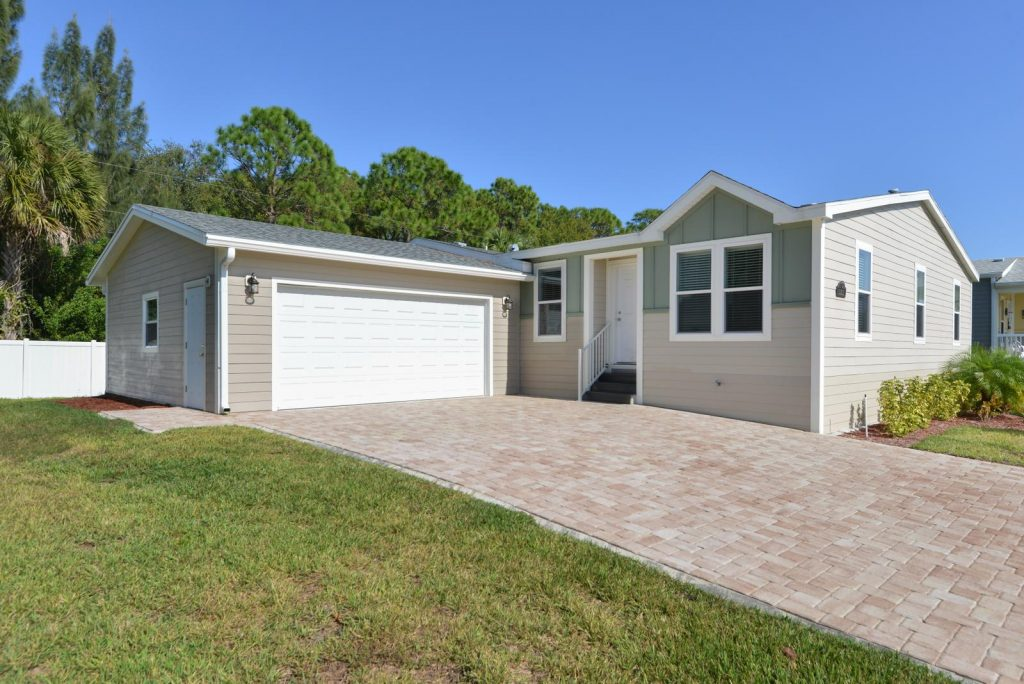 New homes are for sale at Lamplighter Village, an active 55 plus manufactured home community. Front of home with attached 2 car garage. Long driveways of pavers. Green grass and small plants for front landscape. Lush green trees in the background