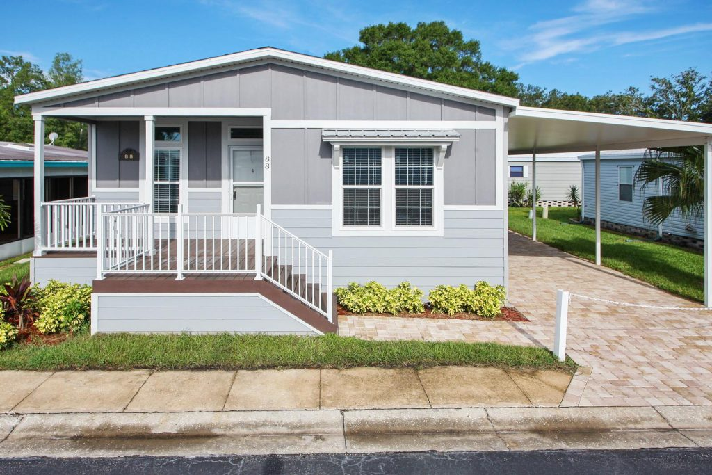 New home that is two tone gray with white trim. Covered porch. Small shrubs planted out front. Covered carport with brick pavers on walkway and driveway.