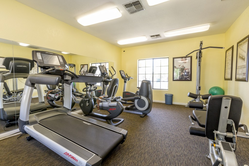 Fitness center with treadmill, stationary bikes and free weight machine.