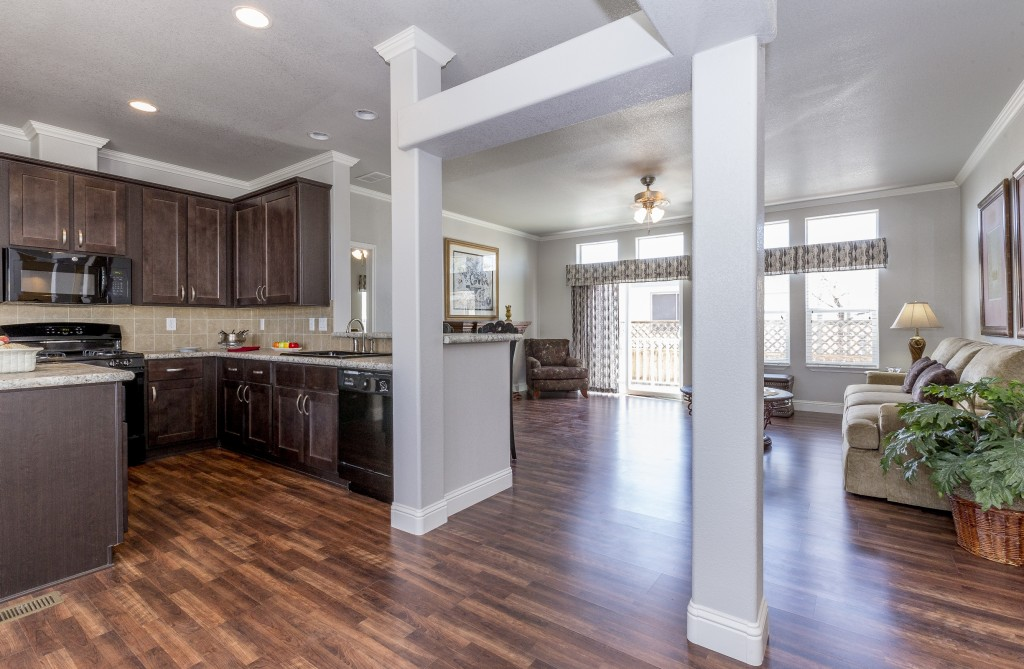 Kitchen with hardwood floors through to the living area. Dark wood cabinets and new black appliances. Granite countertops and tile backsplash. Special white beams give entryway to living area. Recessed lighting.