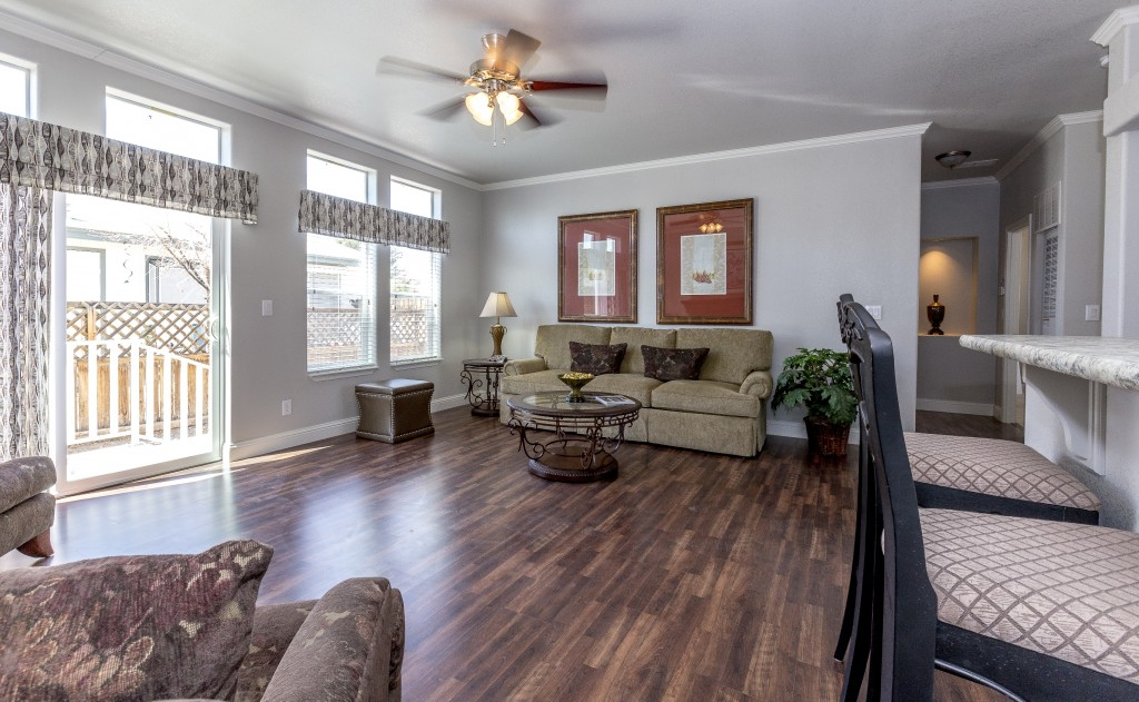 Living room with dark hardwood floors. Loveseat with 2 red pictures hanging above. Tall windows and sliding door to the outside. Small glass coffee table and end table with lamp. Two breakfast nook chairs at kitchen entrance.